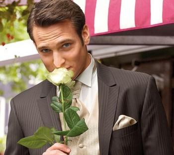 Мужчина в костюме держит белую розу в руках