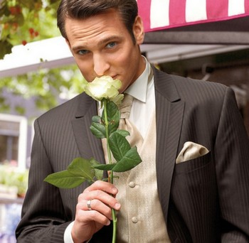 Мужчина в костюме с белой розой в руках