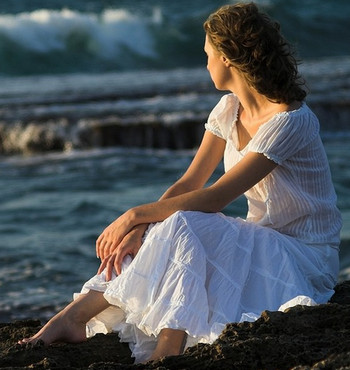 Одинокая женщина на берегу моря
