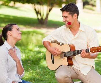 Парень играет девушке на гитаре