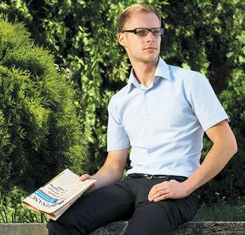 Парень в очках держит в руках газету