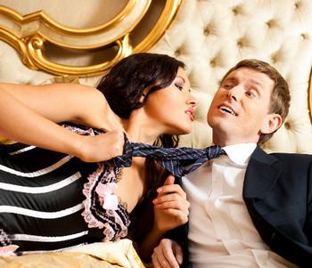 Женщина в кровати тянет мужчину за галстук