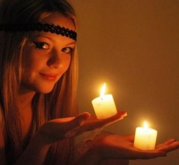 Девушка держит в руках две свечки для заговора