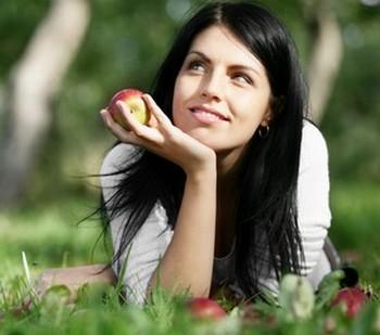 Девушка лежит на траве с яблоком в руках