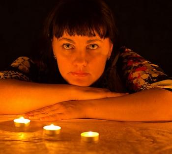 Девушка сидит при свечах