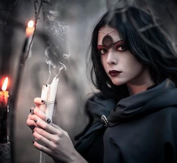 Колдунья в черном со свечами в руках