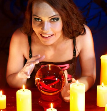 Девушка сидит при свечах с магическим шаром