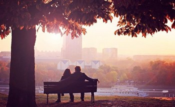 Парень с девушкой сидят на лавочке в парке