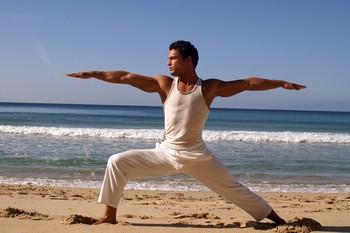 мужчина занимается йогой на пляже