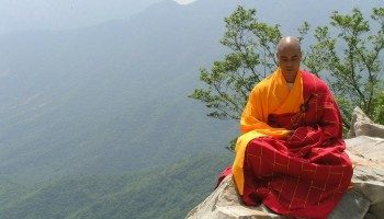 монах медитирует на горе